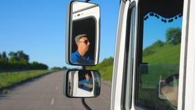 Camionista nos óculos de sol que refletem no espelho lateral de carro movente Homem que conduz a equitação do caminhão ao destino video estoque