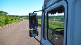 Camionista nos óculos de sol que refletem no espelho lateral de carro movente Homem que conduz a equitação do caminhão ao destino vídeos de arquivo