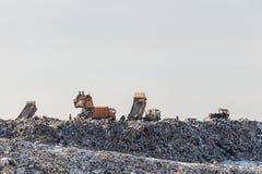 Camions à benne basculante déchargeant des déchets au-dessus de vaste décharge pollution environnementale écologique de photo de  photos stock