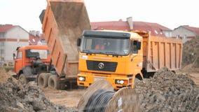 Camions à benne basculante oranges travaillant à un chantier de construction clips vidéos
