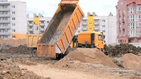 Camions à benne basculante oranges travaillant à un chantier de construction banque de vidéos