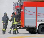 Camions de pompiers et sapeurs-pompiers avec les uniformes et le casque de protection photographie stock libre de droits