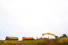 Camions et excavatrice à benne basculante image stock