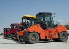 Camions, rouleaux et machines pour l'asphaltage photo stock