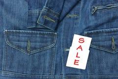 Camisa azul de la mezclilla con la etiqueta de la venta para el fondo fotografía de archivo