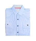 Camisa azul del dril de algodón con un fondo blanco Imagen de archivo libre de regalías