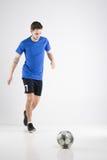 Camisa azul del jugador de fútbol con el estudio aislado bola Imágenes de archivo libres de regalías
