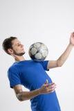Camisa azul del jugador de fútbol con el estudio aislado bola Foto de archivo libre de regalías