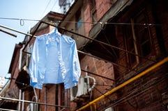 Camisa azul que pendura em uma linha de lavagem em uma aleia tradicional na cidade velha de Shanghai Fotos de Stock Royalty Free