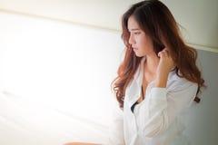 Camisa blanca que lleva de la mujer hermosa elegante que presenta en dormitorio, Fotografía de archivo libre de regalías