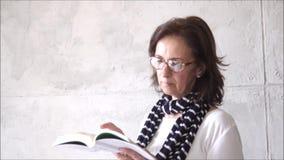 Camisa blanca que lleva de la mujer morena y bufanda azul que leen un libro almacen de metraje de vídeo