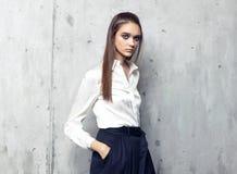 Camisa blanca que lleva del modelo de moda y falda negra larga que presentan en estudio Imagen de archivo libre de regalías