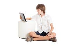 Muchacho adolescente con una PC de la tableta Foto de archivo libre de regalías