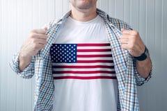 Camisa blanca que lleva del patriota americano con la impresión de la bandera de los E.E.U.U. foto de archivo libre de regalías