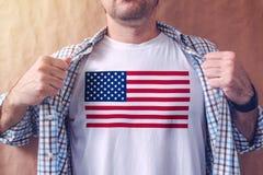 Camisa blanca que lleva del patriota americano con la impresión de la bandera de los E.E.U.U. imagen de archivo