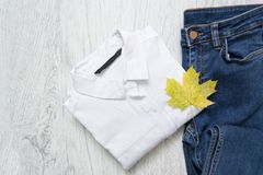Camisa branca, calças de brim e uma folha de bordo conceito elegante Fotos de Stock