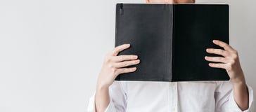 Camisa branca vestindo do homem e guardar um livro preto da tampa na frente dele no lado direito com espaço da cópia imagens de stock
