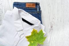 Camisa, calças de brim e folha de bordo brancas clássicas conceito elegante Imagens de Stock Royalty Free