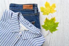 Camisa, calças de brim e folha de bordo branco-azuis listradas conceito elegante Imagem de Stock Royalty Free