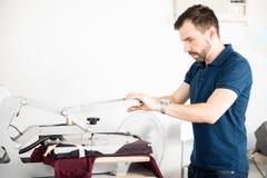 Camisa da impressão do homem em uma oficina fotos de stock royalty free