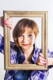 Camisa de algodón azul linda de pelo corto del ` s de los hombres de la mujer que lleva joven que mira a través de marco, sobre e Fotografía de archivo