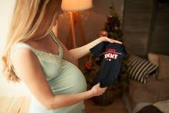 Camisa de los soportes y de los controles de la mujer embarazada para su bebé futuro Foto de archivo libre de regalías