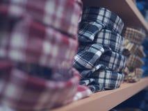 Camisa de tela escocesa en el estante Ropa cuidadosamente doblada El concepto encendido Imagen de archivo libre de regalías