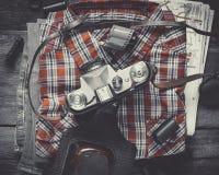 Camisa de tela escocesa, par de tejanos y cámara vieja de la película Imagenes de archivo