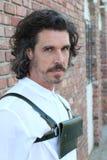 Camisa de vestir del varón adulto y bolso o monedero blanco que lleva modelo en fondo urbano de la pared de ladrillo Foto de archivo