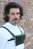 Camisa de vestir del varón adulto y bolso o monedero blanco que lleva modelo en fondo urbano de la pared de ladrillo Imagenes de archivo