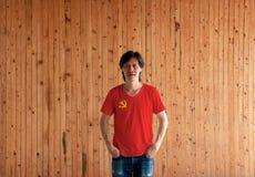 Camisa del color de la bandera del Partido Comunista Chino del hombre que lleva y colocación con dos manos en bolsillos de bragas fotos de archivo