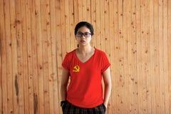 Camisa del color de la bandera del Partido Comunista Chino de la mujer que lleva y colocación con dos manos en bolsillos de braga fotos de archivo libres de regalías