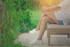 Camisa del desgaste de mujer y mezclilla blancas del cortocircuito, su relajación en silla de madera en el jardín al aire libre r fotografía de archivo