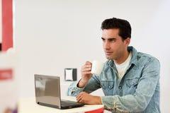 Camisa del dril de algodón del hombre que lleva apuesto que se sienta en una barra de café Fotos de archivo libres de regalías