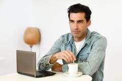 Camisa del dril de algodón del hombre que lleva apuesto que se sienta en una barra de café Imagen de archivo libre de regalías