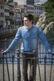 Camisa del dril de algodón del hombre que lleva joven en el puente de la ciudad en Treviso, Italia Foto de archivo