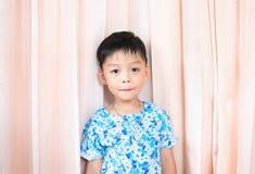 Camisa linda de la flor del desgaste del muchacho en fondo rosado de la cortina Foto de archivo libre de regalías