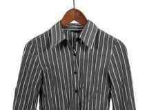 Camisa rayada gris en la percha de madera, aislada foto de archivo