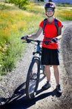 Camisa roja que lleva Biking de la montaña de la mujer Fotografía de archivo
