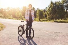 Camisa vestindo e calças de brim do adolescente elegante do moderno que estão na estrada com a bicicleta que aprecia seu passatem Imagem de Stock