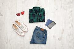 Camisa, vidrios, zapatillas de deporte, vaqueros, teléfono y pasaporte a cuadros azulverdes Fondo de madera concepto de moda Fotografía de archivo