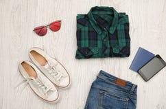 Camisa, vidrios, zapatillas de deporte, vaqueros, teléfono y pasaporte a cuadros azulverdes Fondo de madera concepto de moda Imágenes de archivo libres de regalías