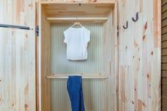 Camisa y pantalones en guardarropa de madera Fotos de archivo