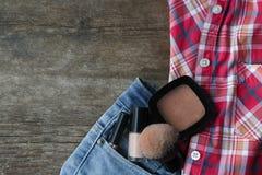 Camisa y vaqueros con los cosméticos en un fondo de madera Fotografía de archivo libre de regalías