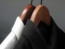 Camisas blancos y negros en perchas de madera imagenes de archivo