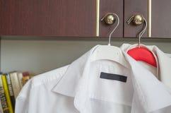 Camisas brancas em ganchos imagem de stock royalty free