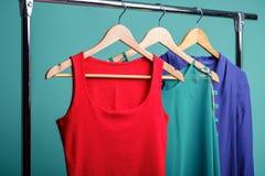 Camisas coloridas do ` s das mulheres nos ganchos de madeira no fundo azul RGB Fotos de Stock