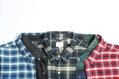 Camisas coloridas dobladas en el fondo blanco fotografía de archivo