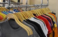 Camisas coloridas em ganchos de madeira no mercado Fotos de Stock Royalty Free