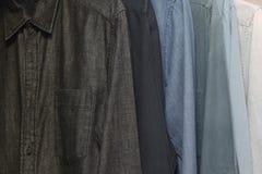 Camisas coloridas penduradas em trilhos Fotos de Stock